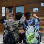 Zwei Jugendliche deuten auf ein Schild am Toilettenhäuschen